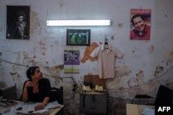 Una mujer mira la fotografía de Fidel y Raúl Castro en su oficina.