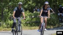 El presidente de Estados Unidos, Barack Obama, y su hija, Malia (d), montan en bicicleta en el Correllus State Bike Path en la isla de Martha's Vineyard, Massachusetts, Estados Unidos.