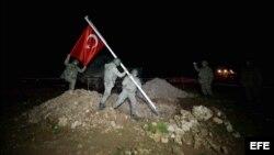Soldados izan la bandera turca en la tumba de Suleimán.