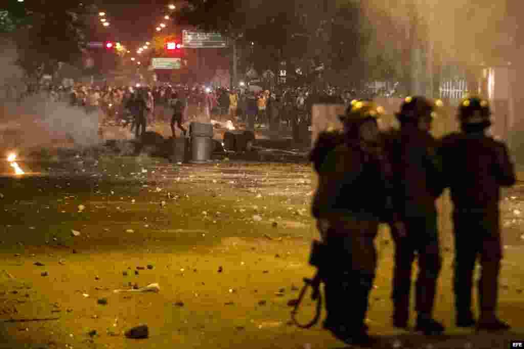 Miembros de la Guardia Nacional Bolivariana (GNB) enfrentan a protestantes hoy, viernes 14 de febrero de 2014.