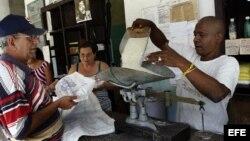 n bodeguero despacha a un anciano el arroz que se distribuye mediante la libreta de racionamiento.