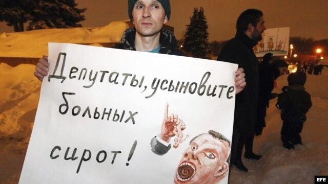 Un manifestante sujeta un cartel en el que se puede leer 'Legisladores, adoptad niños enfermos' durante una manifestación en contra de la ley que prohíbe adoptar niños a Estados Unidos, en San Petersburgo, Rusia.