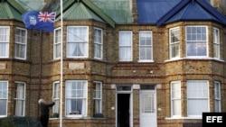 Archivo - Una mujer iza la bandera de las Islas Malvinas frente a la puerta de su casa en Stanley (Islas Malvinas).