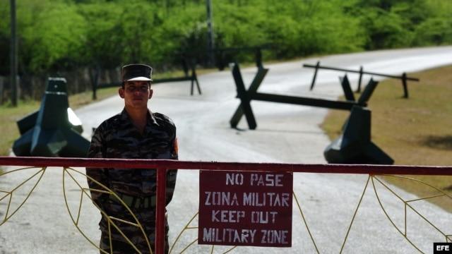 """Soldado cubano custodia entrada al puesto fronterizo """"Punto 8"""", cerca de base naval,  Guantánamo"""
