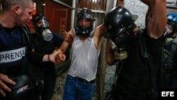 El asistente de cámara de TV Venezuela noticias, Larry Arvelo (c), es auxiliado por otros periodistas tras resultar lesionado durante protestas en Caracas.