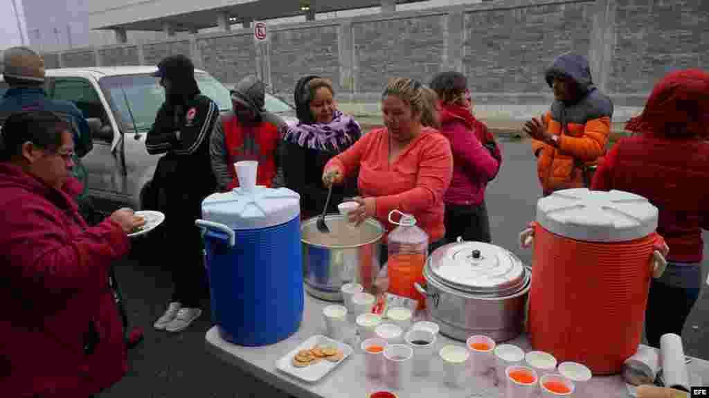n grupo de ciudadanos cubanos reciben alimentos en la línea fronteriza de Nuevo Laredo (México) con territorio estadounidense este lunes 30 de enero de 2017. Decenas de cubanos se reúnen todos los días frente al Puente Internacional Las Américas de la fro