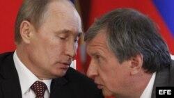 El presidente de Rosneft, la mayor petrolera de Rusia, Ígor Sechin (d), habla con el presidente ruso, Vladimir Putin.