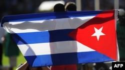 Un deportista cubano celebra su triunfo con la bandera de Cuba.