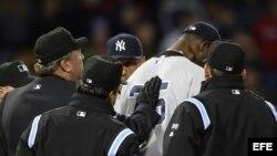 El lanzador de los Yanquis de Nueva York Michael Pineda (2-d) es inspeccionado por el juez Gerry Davis (i).