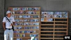 Un hombre vende copias piratas de CDs y DVDs en un pequeño puesto particular en La Habana