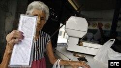 Una anciana muestra su libreta de racionamiento