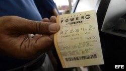 Un hombre muestra un boleto de lotería Powerball.