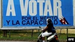 Una mujer pasa frente a un cartel alusivo a las elecciones municipales en Cuba. (Archivo)