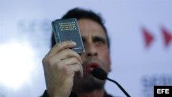 El líder de la oposición venezolana y actual gobernador del estado Miranda, Henrique Capriles, sostiene la Constitución del país durante una rueda de prensa, al conocer la decisión del Tribunal Supremo de Justicia respecto a Chávez.
