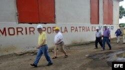 Delegación extranjera pasea frente a un mural con estrofas del himno nacional cubano.