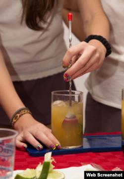 Una joven cubana prepara un trago.