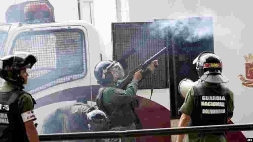 Miembros de la Guardia Nacional Bolivariana (GNB) disparan gas contra manifestantes durante una protesta contra el Gobierno de Nicolás Maduro.