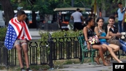 Un joven lleva la bandera de EE.UU. sobre sus hombros en La Habana (Cuba).