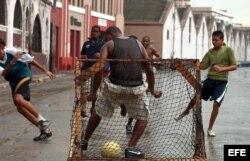 Jóvenes cubanos juegan fútbol soccer.