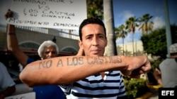 """El cubano Alexander Otero muestra un tatuaje que dice """"No a los Castros"""" durante una vigilia realizada hoy, miércoles 27 de julio 2016, frente al Restaurante Versailles en Miami, Florida."""