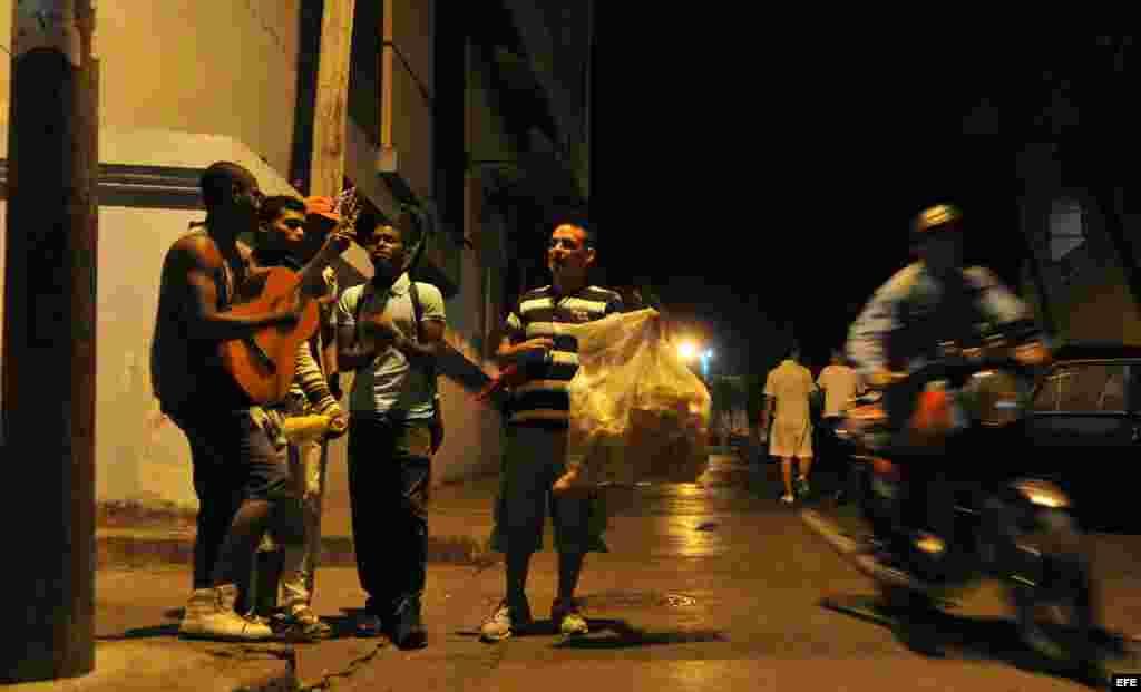 Un grupo de jovenes departe este martes en una calle del centro histórico de Santiago de Cuba (Cuba).