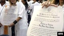 Varios jóvenes médicos muestran sus diplomas de recién graduados.