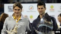 El tenista serbio Novak Djokovic (dcha) y el suizo Roger Federer posan para los fotógrafos tras la final del torneo de tenis de Dubái (Emiratos Árabes Unidos) disputada el sábado 26 de febrero de 2011.