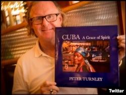El fotógrafo Peter Turnley con su último libro publicado sobre Cuba.