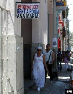 Varias personas pasan junto a un cartel de renta de habitaciones en La Habana