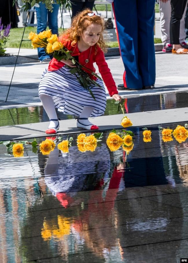 Una niña deposita flores en el Monumento a los Héroes Caídos, en Boston, Massachusetts.