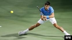 El tenista serbio Novak Djokovic devuelve la bola.
