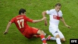 El jugador polaco Rafal Murawski disputa el balón con Alan Dzagoev (i) de Rusia hoy, martes 12 de junio de 2012, durante el juego del Grupo A de la Eurocopa 2012, que se disputa en Varsovia (Polonia).