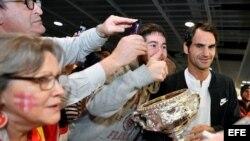 El tenista suizo Roger Federer (d) posa con los fans que le aguardaban a su llegada al aeropuerto de Zúrich (Suiza), el 31 de enero de 2017.