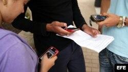 Tres jóvenes usan sus teléfonos móviles en La Habana (Cuba).
