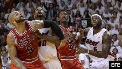 Los jugadores de los Heat Dwyane Wade (i) y Udonis Haslem (d) ante Carlos Boozer (c) de los Bulls hoy, miércoles 8 de mayo de 2013, durante la fase final de la NBA en el American Airlines Arena de Miami, Florida (EE.UU.).