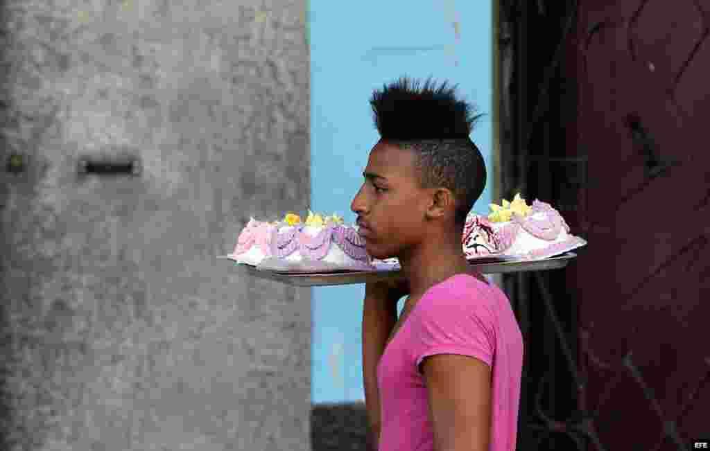 Un joven camina vendiendo tortas el miércoles 31 de diciembre de 2014, en La Habana (Cuba).