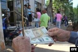 Un hombre muestra un peso convertible cubano y un dólar estadounidense frente a una oficina de la Western Union en La Habana.