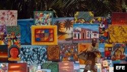 Lustrabotas haitiano camina por la avenida del malecón, frente a pinturas haitianas que son exhibidas para la venta a turistas en República Dominicana.