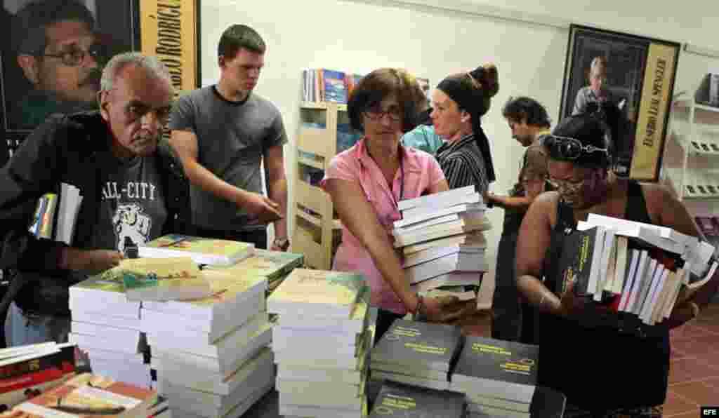 Varios asistentes a la Feria del Libro en busca de algunos de los más de 2.000 títulos a la venta, trabajadores en el evento.