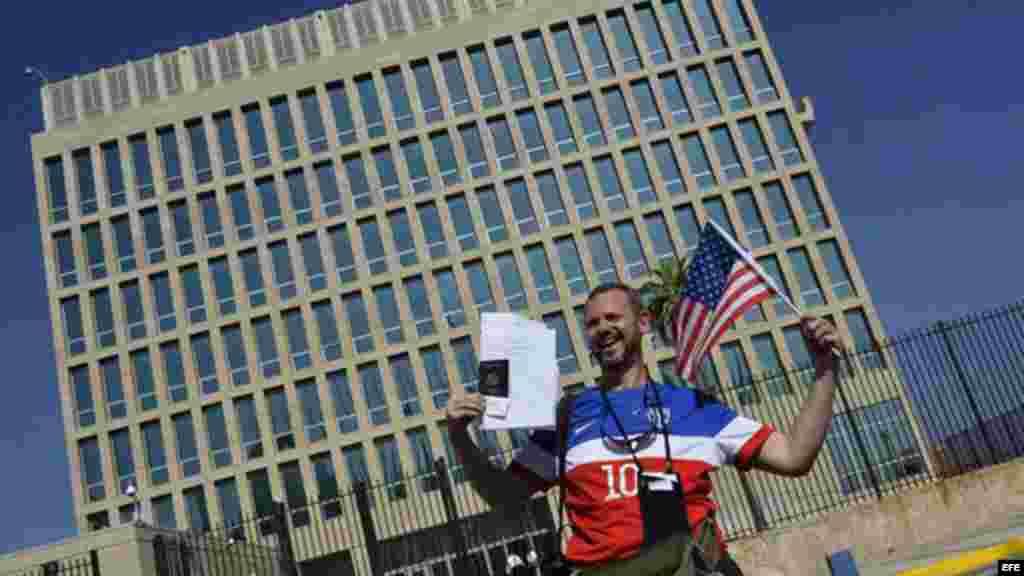 Un hombre posa con sus documentos migratorios frente a la Embajada de los EEUU