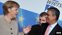La canciller alemana Angela Merkel (i) conversa con el vice presidente del Deutsche Bank, Anshu Jain, a su llegada a un Consejo Económico del CDU, en Berlín, Alemania.EFE/Hannibal Hanschke