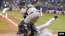 El jugador de Tampa Bay Matt Joyce (L) se desliza en el home frente al receptor de los Yankees de New York Austin Romine (R).