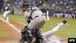 El jugador de Tampa Bay Matt Joyce (L) se desliza en el home frente al receptor de los Yankees de New York Austin Romine (R). Archivo.