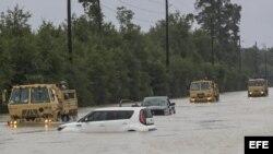 Camiones de la Guardia Nacional de Texas que llevan a víctimas de inundaciones pasan junto a vehículos sumergidos después del paso del huracán Harvey en Houston, Texas, Estados Unidos, 29 de agosto de 2017. El huracán Harvey llegó a tierra en la costa sur