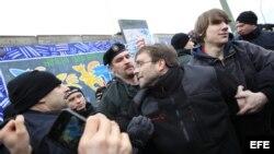 Manifestantes protestan mientras desmantelan una sección del muro de Berlín en Alemania.