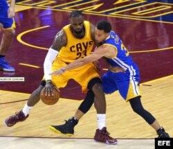 El jugador de Warriors Stephen Curry (d) marca a LeBron James (i), de Cavaliers, durante el cuarto partido de la Serie Final de la NBA entre Warriors y Cavaliers.