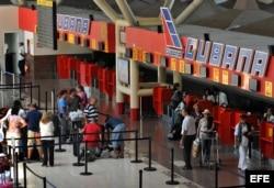 Varias personas hacen cola en el mostrador de la aerolínea Cubana de Aviación, en el aeropuerto José Martí, de La Habana (Cuba).