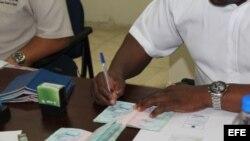 Un funcionario del Servicio Nacional de Migración de Panamá otorga permisos especiales de salida a migrantes cubanos.