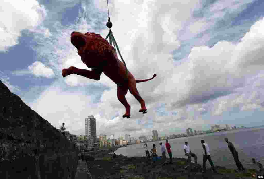 """El artista plástico cubano Roberto Fabelo (i) posa junto a un león rojo creado por él que conforma la obra """"Garras en la piedra"""" que se instala en los arrecifes del malecón de La Habana (Cuba). Esta pieza forma parte"""