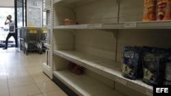Un hombre ingresa a un supermercado con estanterías desabastecidas febrero de 2013, en Caracas (Venezuela). los ciudadanos se afanan en la búsqueda de pollo, harina, leche o azúcar.